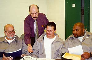 Joe Marinello (standing), contracted instructor  at Albemarle Correctional Institution, talks with inmates Larry Phifer (from left to right), James Rogers and Walter McDowell.  The inmates recently graduated from S.T.O.P. and Change Direction, a program aimed at educating offenders about domestic violence.
